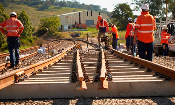 image of a new section of track being laid with track workers wearing orange hi vis clothing
