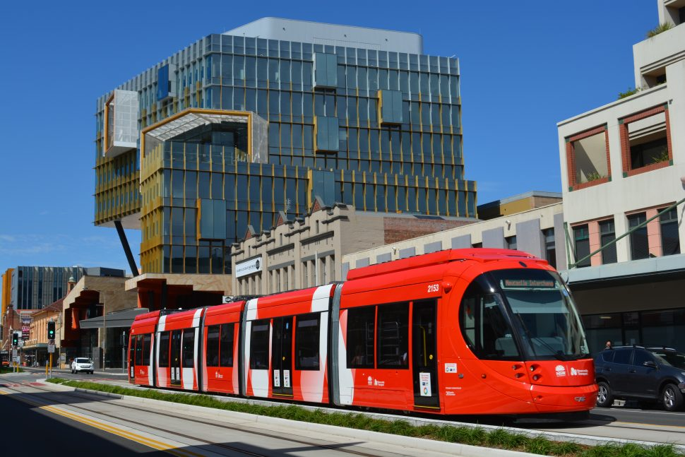 Image of a red Newcastle Light Rail vehicle moving through a road section of track surrounded by buildings and a beautiful blue sky in Newcastle, NSW