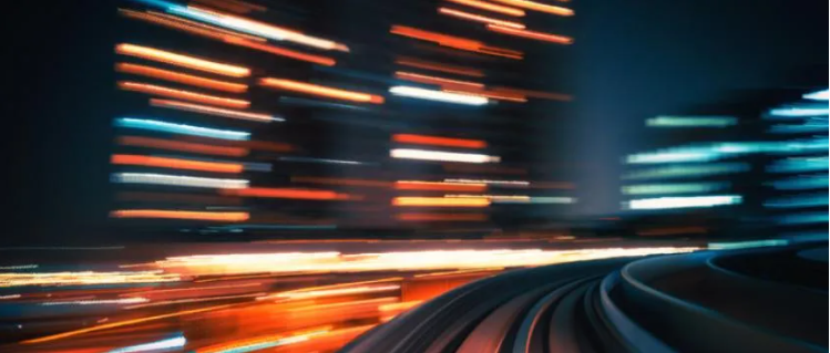 long exposure image of a train track moving fast past light up buildings creating light trails