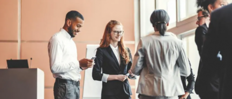 a stock image of three people in business wear networking and having a conversation