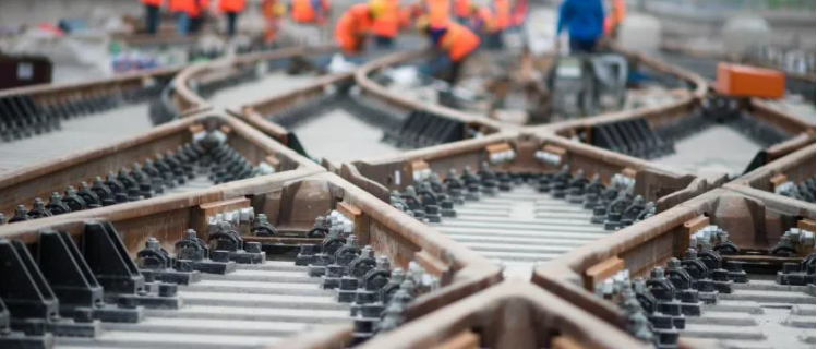 Close up image of multiple tracks converging at multiple points with orange track workers in the distance